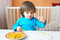 Stock Image : Little boy made macaroni beads