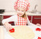 Stock Image : Little girl cuts dough with form for cookies