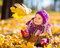 Stock Image : Little girl playing with autumn leaves