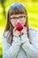 Stock Image : Little girl portrait eating red apple in garden.