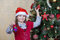 Stock Image : Little girl in Santa hat near Christmas tree