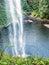 Stock Image : Looking through a waterfalls at wooden foot bridge