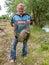 Stock Image : Man fisherman caught a large freshwater carp. Fisherman with tro