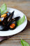 Stock Image : Mussels served white plate garnished with fresh basil