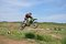 Stock Image : MX rider on the motorbike takes off from the hill
