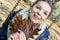 Stock Image :  O adolescente de sorriso com carvalho marrom sae nas mãos