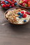 Stock Image : Oatmeal, granola, nuts and berries in bowls on wooden background