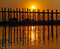 Stock Image : An old figure crossing the U-Bein bridge at sunset, Amarapura, Myanmar (Burma).