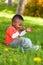 Stock Image : Plenerowy portret śliczna młoda mała czarna chłopiec bawić się z