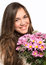 Stock Image : Portrait of a beautiful girl with long hair and a pink flowers