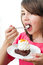 Stock Image : Portrait of young woman eating cake isolated on wh