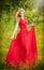 Stock Image :  Portret młoda piękna blondynki kobieta jest ubranym długą czerwoną elegancką suknię pozuje w zielonej łące Modny seksowny atrakcy