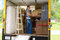 Stock Image : Pretty woman loading a full moving truck