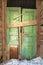 Stock Image :  Puerta verde torcida en casa de madera vieja
