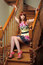Stock Image : Red haired woman sitting on wodden stairs