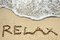 Stock Image : Relax written on sandy beach near sea - holiday concept