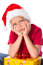 Stock Image : Sad boy with gift box in christmas hat