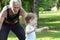 Stock Image : Senior man grandfather chasing grandson in park