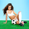 Stock Image : Sexy busty tanned brunette with a soccer ball