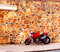 Stock Image : Shiny Red Motorcycle Parked By Stone Wall