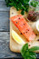 Stock Image : Slice of Salmon with basil and pepper on the board
