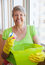 Stock Image : Smiling elderly woman cleaning a window