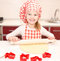 Stock Image : Smiling little girl with chef hat rolling dough
