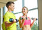 Stock Image : Smiling man and woman with dumbbells in gym