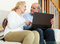 Stock Image : Smiling mature couple  with laptop