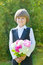 Stock Image : Smiling schoolboy in school uniform with flowers