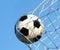 Stock Image : Soccer ball in goal net over blue sky. Football.