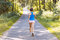 Stock Image : Sporty young woman runner running on the road