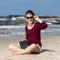 Stock Image : Teenage girl reading book sitting on beach