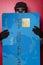 Stock Image : Thief hiding behind big blue credit card