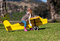 Stock Image : Three-year-old girl on yellow toy airplane outdoors