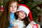 Stock Image : Two adorable girls in front of christmas tree