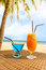 Stock Image : Two fresh cocktail on a beach under palm tree