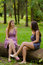 Two girls talking while sitting in the forest