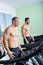 Stock Image : Two handsome men in gym running on the ergometer