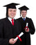 Stock Image : Two male graduates with scrolls, isolated on white