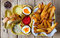 Stock Image : Two soft boiled eggs with fries and sauces.