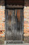 Stock Image : Weathered Gray Door in a Brick Wall