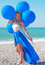 Stock Image : Woman holding bunch of  air balloons at the beach