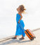 Stock Image : Young woman with suitcase on the pier