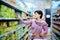 Stock Image : Woman pushing shopping cart choosing at goods in supermarket