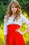 Stock Image : Woman in red skirt standing under the tree