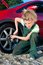 Stock Image : Woman repairing a car, unscrew the wheel