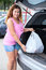 Stock Image : Woman shopper loading bag in trunk of her suv