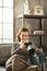 Stock Image : Woman sitting on divan and using dslr photo camera
