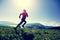 Woman trail runner running on beautiful mountain peak